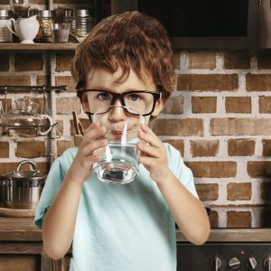 A boy drinking a glass of conditioned water