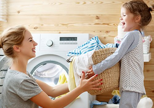 A mom and daughter remove clean, soft laundry from the dryer with the caption that reads, Clean Water for Your Entire Home.