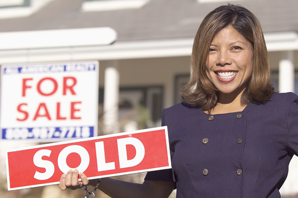"A real estate agent shows off a ""SOLD"" sign after selling a new home."